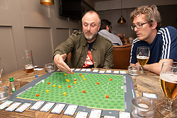 Edinburgh football fan and game designer Colin Webster has designed a brand-new football strategy game called Counter Attack. Last night he hosted a game session in Leith to demonstrate the game to a few interested players. The game is currently on the crowd-funding site Kickstarter and on track to meet it's funding target. If so, Colin hopes the gamne will be available by August this year. Pictured: A game in progress<br /> <br /> <br /> © Jon Davey/ EEm