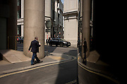Reflected in a curved window, a man walks along a narrow side street at the junction of King William Street in the City of London, the capital's Square Mile, and its financial heart.