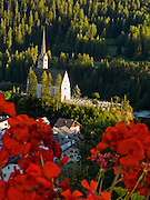 """Red geraniums frame the main church and cemetery in the town of Scuol, Switzerland, Europe. Published in Ryder-Walker Alpine Adventures """"Inn to Inn Alpine Hiking Adventures"""" Catalog 2007."""