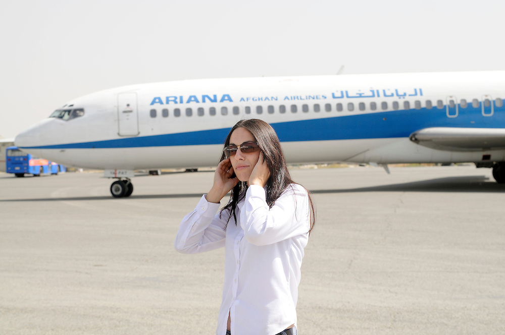 """Pilot, Danielle Aitchison, covers her ears while an Ariana Afghan Airlines Boeing 727 taxis for takeoff at Kabul International Airport.  Danielle flies in Afghanistan for The United Nations Humanitarian Air Service (UNHAS).   ...When asked about flying in a war zone, she says,  """"I'm just a normal average female.  My job is maybe a little different to some, but I have the same feminine side as other women.  I don't have any trouble going back to New Zealand relating to people.  I'm just a regular chick.""""."""