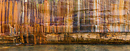 A large rock mural painted with minerals leaching from the sandstone cliffs of Pictured Rocks National Lakeshore