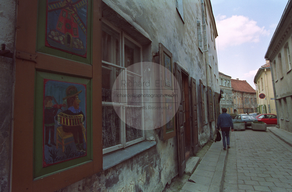 A man walks down a small street past a house with folkart painted shutters in Riga, Latvia.