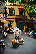 A Vietnamese woman wearing a conical hat carries a yoke loaded with fruits, Hanoi, Vietnam, Southeast Asia