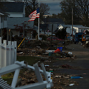 Wreckage from Superstorm Sandy - including cars, roofs, house-walls and personal effects -  litters the streets of Union Beach, NJ.  The storm-surge from Superstorm Sandy destroyed several oceanfront blocks of Union Beach, leveling homes or lifting them off their foundations, breaking them apart and moving them.