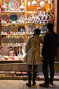 Couple viewTurkish ceramics vases bowls in window of shop in Kucukayasofya Caddesi in Sultanahmet, Istanbul, Turkey