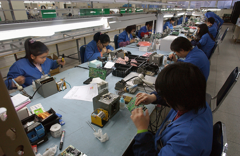 TAISHAN, CHINA-FEBRUARY 12: Workers assemble computer chip motherboards at Mah Electronics on February 12, 2005 in Taishan, China.  Increasing amounts of outsourcing from Computer manufacturers in the United States has given many mainland Chinese workers employment with better conditions, education and benefits .   Photo by David Paul Morris