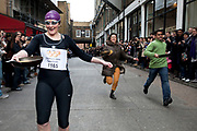 Great Spitalfields Pancake Race on Shrove Tuesday, pancake day, at the Old Truman Brewery, London, UK. This is a fun quirky annual event where competitors come as teams of four people dressed up in costume of some kind. Organised by Alternative Arts raising money for charity.