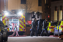 © Licensed to London News Pictures. 02/01/2021. London, UK. Armed police walk past a fire engine in a staging area close to the incident scene. Police attended a call 14:12 GMT on Saturday 2nd January to a disturbance at Great Dover Street, SE1. Due to threats made to officers, a multi-agency response was coordinated. Photo credit: Peter Manning/LNP