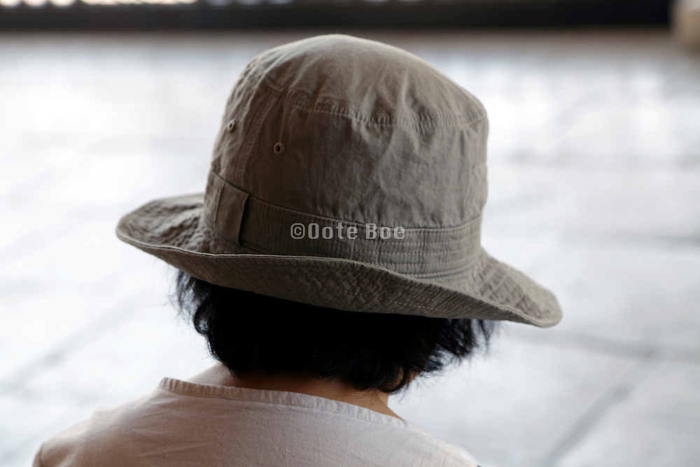 Asian woman with hat seen from behind