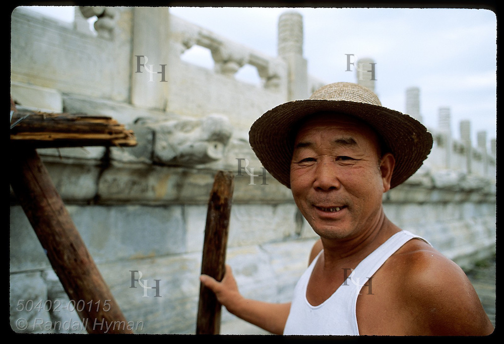 Man in undershirt & straw hat glances at camera while repairing wall in Forbidden City; Beijing China