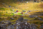 A shaft of sunlight illuminates the small village in Kjerkfjorden, Moskenesoya, Lofoten Islands, Norway.