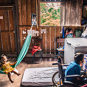 Lukas watching TV with her sister in the small border village of Cucuì, triple border Brazil, Colombia and Venezuela