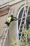 Workers secure hurricane shutters on a historic church in preparation for Hurricane Irma September 8, 2017 in Charleston, South Carolina. Imra is expected to spare the Charleston area but hurricane preparations continue as Irma leaves a path of destruction across the Caribbean.