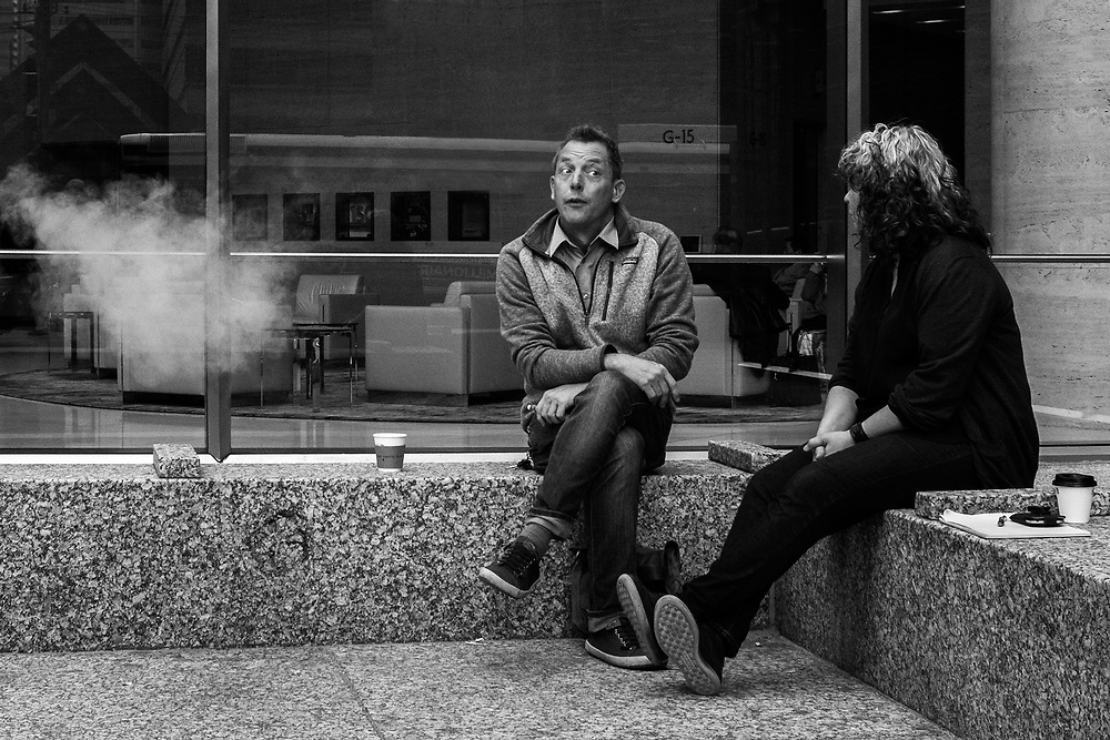Capturing moments like this is all about anticipation. I saw these two people having a lively conversation engaging in laughter and jokes. Hoping for some interesting gestures I waited and made several photographs. This was the one I choose as the expression on the man's face was fabulous and the puff of smoke added some mystery.