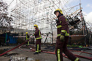 London Fire fighter aqttend to smouldering remains after an inner-city estate fire in south London. About 310 people were forced to leave their homes after the fire engulfed a wooden structure under construction in scaffolding at Sumner Road and Garrisbrooke Estate, Peckham, London at about 0430 AM. It spread to two blocks of maisonettes and a destroyed a pub. More than 150 firefighters tackled this unusually large and ferocious fire which injured ten people, including two police officers who received hospital treatment for minor injuries.  .