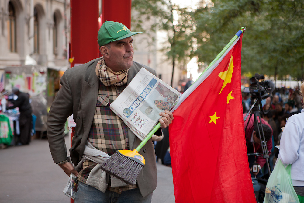 A caucasian man holds a Chinese flag on a broomstick flagpole along with a stack of the China Daily newspaper.