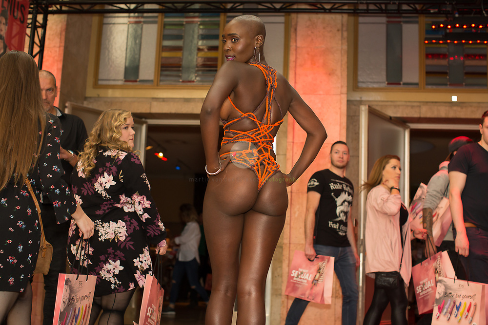 Berlin Expo Center, Berlin, GERMANY, 13.10.2018 - A woman posing for the photographers, while other visitors watch on. The VENUS Berlin Fair is among the largest international erotic trade fairs, with more than 250 exhibitions from 40 countries and 30,000 visitors.