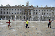 Children playing with water pistols in the fountains at Somerset House in London, UK. The United Kingdom's national weather service forecast temperatures reaching a high of 21 degrees Celsius (69.8 degrees Fahrenheit) in London on Saturday. Unseasonally high spring temperatures for the time of year.