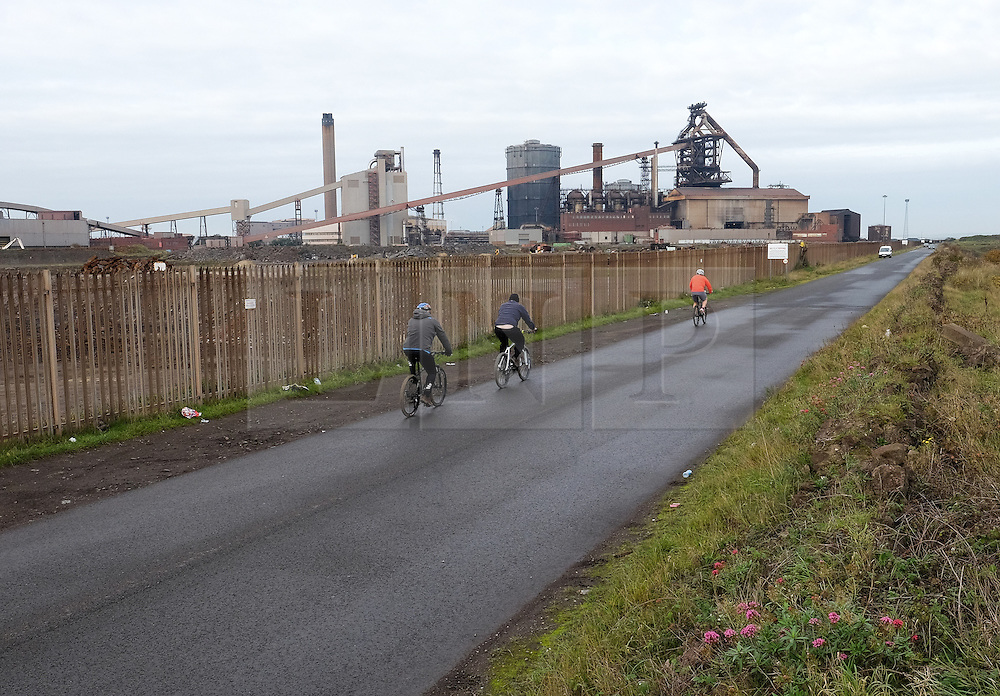 © Licensed to London News Pictures.20/10/15<br /> Redcar, UK. <br /> <br /> Cyclists ride along the road to South Gare in front of the recently closed SSI UK steel blast furnace in Redcar, England. The closure of the site marks the end of 170 years of steel making heritage on Teesside and was the first of a number of recent closures of steel making plants across the UK.<br /> <br /> Photo credit : Ian Forsyth/LNP