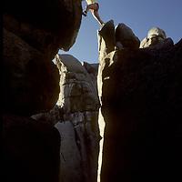 Lois Fischer steps over rock chasm in Buttermilk rocks near Bishop, California.