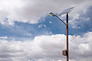 A solar powered light pole stands against a partly cloudy sky at an Interstate - 70 rest area in the San Rafael Swell of Utah, USA