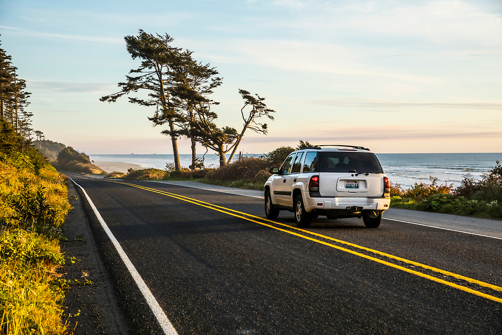 A car driving south on highway 101 along the Olympic Peninsula coast as the sun sets over the Pacific Ocean, Washington, USA.