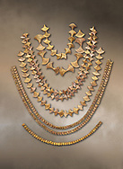 Mycenaean gold necklaces from the Mycenae chamber tombs, Greece. National Archaeological Museum Athens.<br /> <br /> From top to bottom: <br /> <br /> Top four  necklaces in the shape of papyrus flowers .<br /> <br /> Fifth necklace down in the shape of Ivy leaves from tomb 91 Cat No 3186<br /> <br /> <br /> Bottom necklace with beads in the shape of hangimng scrolls from tomb 25 Cat No 2478. .<br /> <br /> If you prefer to buy from our ALAMY PHOTO LIBRARY  Collection visit : https://www.alamy.com/portfolio/paul-williams-funkystock/mycenaean-art-artefacts.html . Type -   Athens    - into the LOWER SEARCH WITHIN GALLERY box. Refine search by adding background colour, place, museum etc<br /> <br /> Visit our MYCENAEN ART PHOTO COLLECTIONS for more photos to download  as wall art prints https://funkystock.photoshelter.com/gallery-collection/Pictures-Images-of-Ancient-Mycenaean-Art-Artefacts-Archaeology-Sites/C0000xRC5WLQcbhQ