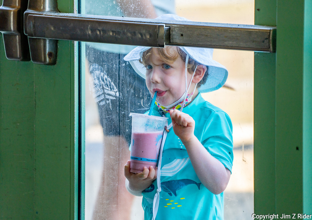 A little boy enjoys a cool drink as he takes in the atmosphere along the boardwalk.