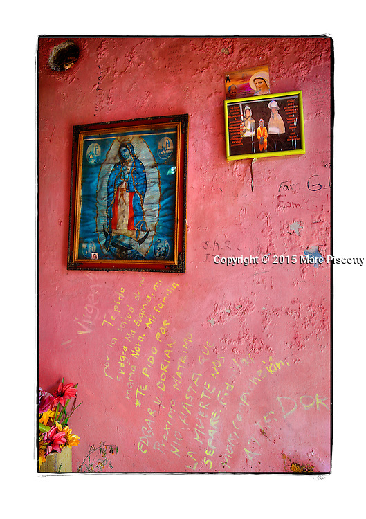"""SHOT 2/6/15 11:51:54 AM - A roadside capilla in the mountains just outside of Mascota, Mexico and featuring Nuestra Señora de Guadalupe as well as pictures of loved ones and personal notes. The Virgin of Guadalupe has symbolized the Mexican nation since Mexico's War of Independence. Our Lady of Guadalupe (Spanish: Nuestra Señora de Guadalupe) is a celebrated Catholic icon of the Virgin Mary also known as the Virgin of Guadalupe (Spanish: Virgen de Guadalupe). The Lady of Guadalupe is of significant importance to Mexican Catholics and has been given the titles of """"Queen of Mexico"""", """"Empress of the Americas"""", and """"Patroness of the Americas"""". Roadside capillas, or tiny chapels, are common along the roads and highways of Mexico which is heavily Catholic and are often dedicated to certain patron saints or to the memory of a loved one that has passed away. Often times they contain prayer candles, pictures, personal artifacts or notes. (Photo by Marc Piscotty / © 2015)"""