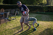 An eight year-old boy plays rough and tumble with his dad in an English Summer garden, on 5th May 2018, in Wrington, North Somerset, England.