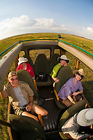 Tourists in an open topped safari vehicle, Masai Mara National Reserve, Kenya