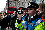 Police cameraman records the protest on a small camcorder. Disabled and able bodied demonstrators chain themselves together and block Oxford Circus in central London. Protesting at the Tory parties Welfare Reform Bill (WRB) which the government plans to make law by May 2012 could leave thousands destitute. It will affect disabled people badly with a cap on benefits and cutting additional support despite promises not to do so.