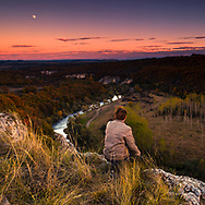 Man is sitting on a edge of river canyon and looking at the full moon