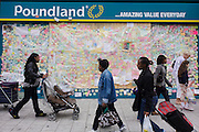 Local Peckham shoppers pass-by the spontaneous messages of love on the Poundland peace wall after the London riots. In response to the violence and destruction that took place the week before, communities reacted with anger in a way rarely seen in a large UK city these days. The messages vary in their sentiment but generally echo a sense of disgust at the looting and rioting with brief notes of co-operation, advice and communal encouragement. Walls like these have sprung up in other locations where destruction was widespread and locals lost their convenience stores, sports shops and even homes.
