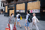 As Britain enters a period of deep recession, with some shops closing either temporarily or permanently as the economic downturn caused by the Covid-19 pandemic cuts hard, entertainment venues in the West End at Leicester Square remain boarded up and closed on 13th August 2020 in London, United Kingdom. The Office for National Statistics / ONS has announced that gross domestic product / GDP, the widest gauge of economic health, fell by 20.4% in the second quarter of the year, compared with the previous quarter. This is the biggest decline since records began. The result is that Britain has officially entered recession, as the UK economy shrank more than any other major economy during the coronavirus outbreak.
