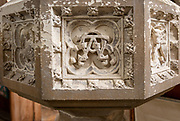 Historic interior of East Bergholt church, Suffolk, England, UK baptismal font stonework detail alpha omega symbol