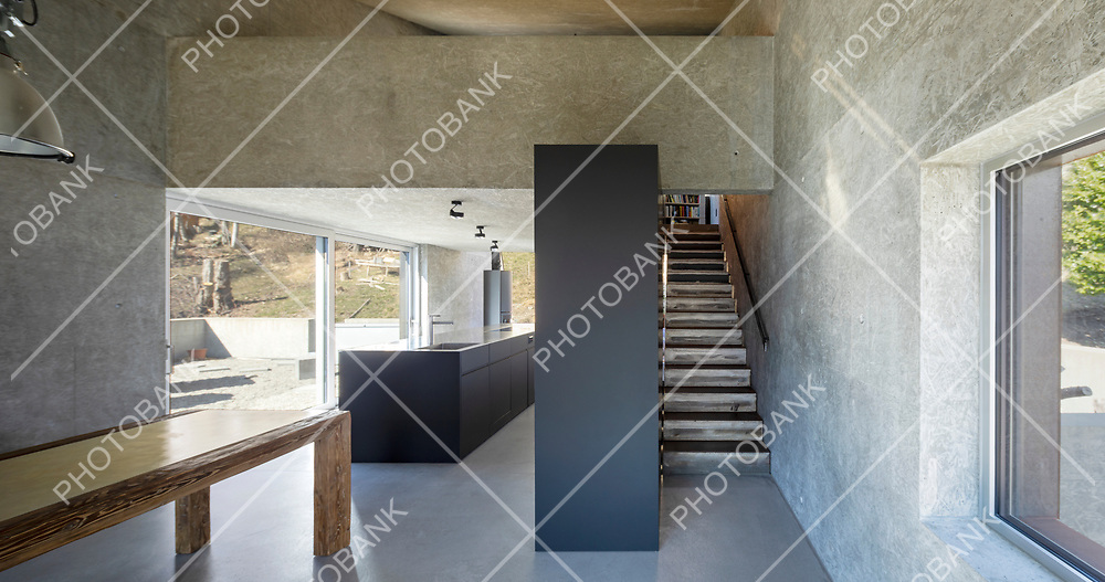 Front view of open space in modern villa with kitchen, minimal stairs and table. Large windows. Nobody inside