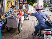 """04 OCTOBER 2012 - BANGKOK, THAILAND: A motorcyclist picks up a """"to go"""" order from a street food stall on Sukhumvit Soi 22 in central Bangkok. Thailand in general, and Bangkok in particular, has a vibrant tradition of street food and """"eating on the run."""" In recent years, Bangkok's street food has become something of an international landmark and is being written about in glossy travel magazines and in the pages of the New York Times.       PHOTO BY JACK KURTZ"""