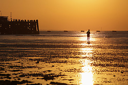 © Licensed to London News Pictures. 01/10/2015. Southsea, Hampshire, UK. A man running on the beach at Southsea in Portsmouth enjoying the sunrise this morning, 1st October 2015, on what is set to be another dry and fine day in the south of England. Photo credit : Rob Arnold/LNP