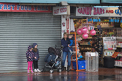 © Licensed to London News Pictures . 17/06/2015. Blackpool  , UK . A woman and children shelter from rain in a shop doorway . Rain and fog over Blackpool today ( Wednesday 17th June 2015 ) . Photo credit : Joel Goodman/LNP