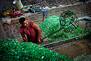 A man washes chips of ground plastic from recycled bottles.