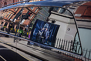Reflected in a limousine car window is a construction hoarding featuring a male with a bird of prey on his arm, on 23rd September 2016, in Mayfair, central London, England.