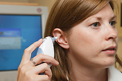 Woman at work taking temperature with digital thermometer in her ear.