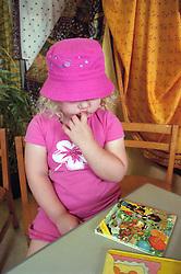 Nursery school girl sitting at desk in classroom sucking finger,
