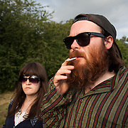 A man with a big red beard and stripy shirts smokes in the dying sun light. Audience listens to live music in the late sun on a hot summers day at Super Normal art festival in Oxfordshire on the land of the Braziers Park. The festival is a mix of live music and performance art.
