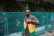 A man carrying his bottle of Jack Daniels on his head on Sunday 28th August 2016 at the 50th Notting Hill Carnival in West London. A celebration of West Indian / Caribbean culture and Europes largest street party, festival and parade. Revellers come in their hundreds of thousands to have fun, dance, drink and let go in the brilliant atmosphere. It is led by members of the West Indian / Caribbean community, particularly the Trinidadian and Tobagonian British population, many of whom have lived in the area since the 1950s. The carnival has attracted up to 2 million people in the past and centres around a parade of floats, dancers and sound systems.