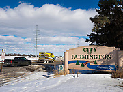 "26 FEBRUARY 2020 - FARMINGTON, MINNESOTA: The sign welcoming people to Farmington, MN, about 30 minutes south of the Twin Cities. Farmington, with a population of 21,000, is a farming community that has become a Twin Cities suburb, the population has doubled since the 2000 census. The city lost its only grocery store, a Family Fresh Market, in December, 2019. The closing turned the town into a ""food desert."" The USDA defines food deserts as having at least 33% or 500 people of a census tract's population in an urban area living 1 mile from a large grocery store or supermarket. Grocery chains Hy-Vee and Aldi both own land in Farmington but they have not said when they plan to build or open stores in the town.     PHOTO BY JACK KURTZ"