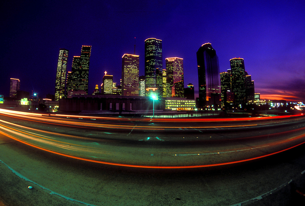 Evening traffic passing by on the western side of Houston, Texas with downtown skyline.