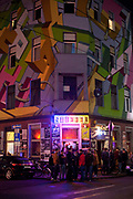 Bar on trendy Zulpicherstrasse, with young people standing outside, night shot, Cologne.