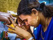 28 OCTOBER 2015 - YANGON, MYANMAR: A woman prays by touching her forehead to the finger of a statue during observances of Thadingyut at Botataung Pagoda in Yangon. Botataung Pagoda was first built by the Mon, a Burmese ethnic minority, around the same time as was Shwedagon Pagoda, over 2500 years ago. The Thadingyut Festival, the Lighting Festival of Myanmar, is held on the full moon day of the Burmese Lunar month of Thadingyut. As a custom, it is held at the end of the Buddhist lent (Vassa). The Thadingyut festival is the celebration to welcome the Buddha's descent from heaven.    PHOTO BY JACK KURTZ